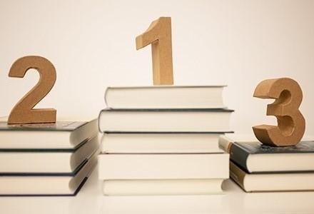 aus Büchern gebaute Siegertreppe mit Holzzahlen